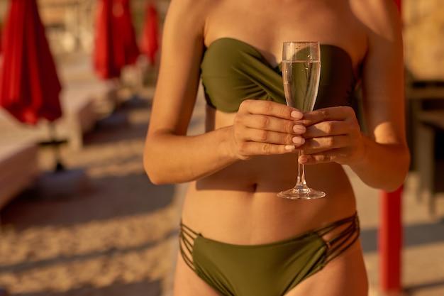 Jeune femme en maillot de bain avec un verre à la main sur la plage de la ville reste sur la station balnéaire