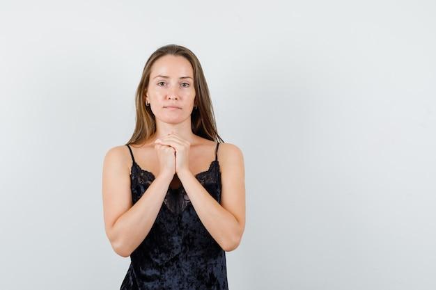 Jeune femme en maillot noir debout avec les mains jointes et à la calme