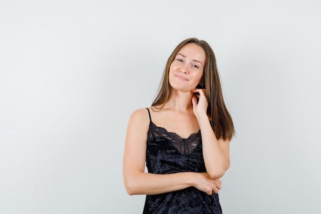 Jeune femme en maillot noir touchant le cou avec les doigts et à la recherche positive