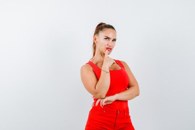 Jeune femme en maillot rouge, pantalon rouge tenant le doigt sur la bouche et regardant pensif, vue de face.