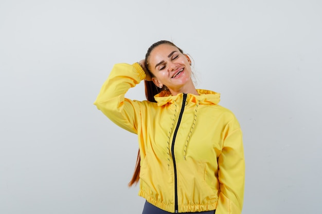 Jeune femme avec la main derrière la tête en veste jaune et charmante, vue de face.