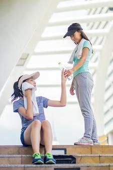 Jeune femme à la main donnant une bouteille d'eau potable froide