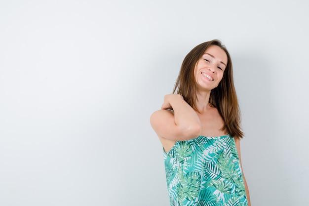 Jeune femme avec la main sur l'épaule en blouse et l'air gaie, vue de face.