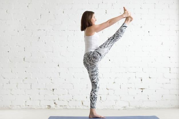 Jeune femme en main étendue à big toe pose, profil