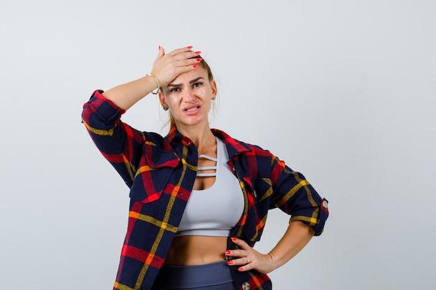 Jeune femme avec la main sur le front en haut, chemise à carreaux et oublieuse. vue de face.