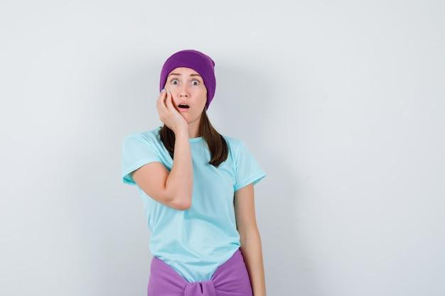 Jeune femme avec la main sur la joue, gardant la bouche ouverte en t-shirt bleu, bonnet violet et l'air surpris. vue de face.