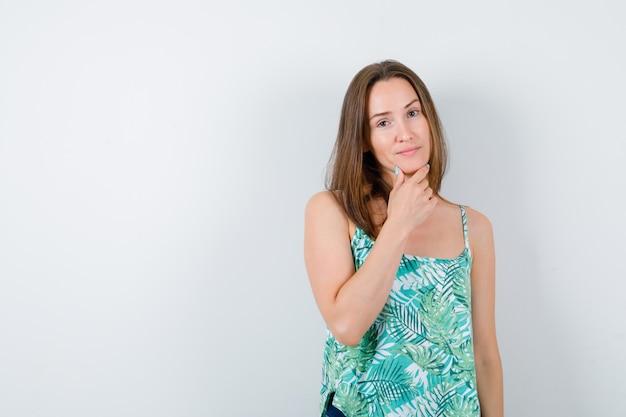 Jeune femme avec la main sur le menton et l'air confiant, vue de face.