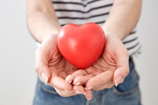 Jeune femme main montrant le coeur rouge