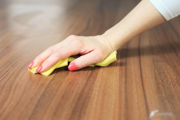 Jeune femme main nettoyage table en bois moderne par chiffon à poussière