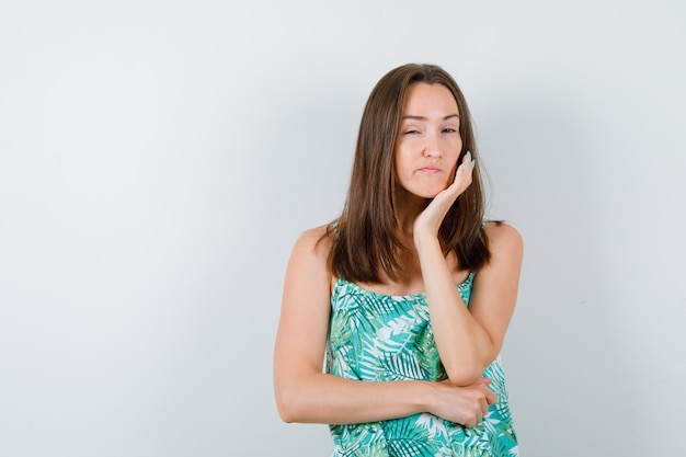 Jeune femme avec la main sous le menton en blouse et à la pensive , vue de face.