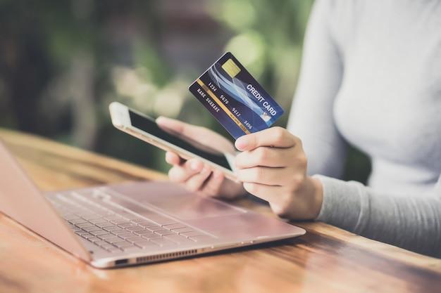 Jeune femme main tenant une carte de crédit en plastique et utilisant un ordinateur portable. achats en ligne ou concept de paiement.