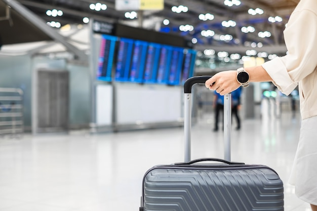 Jeune femme main tenant la poignée de bagage avant de s'enregistrer à l'aéroport