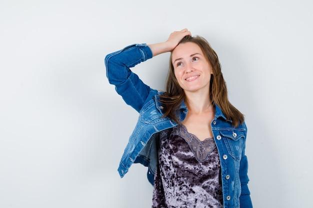 Jeune femme avec la main sur la tête, levant la veste en jean et l'air rêveuse. vue de face.