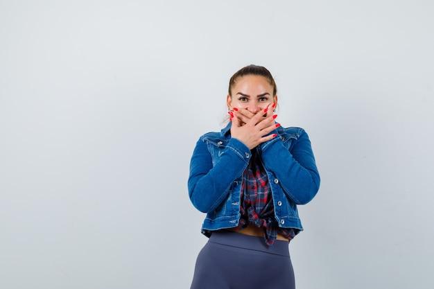 Jeune femme avec les mains sur la bouche en chemise à carreaux, veste, pantalon et l'air étonné. vue de face.