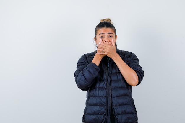 Jeune femme avec les mains sur la bouche en doudoune et l'air choqué, vue de face.