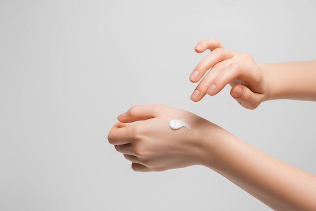 Jeune femme mains avec de la crème. femme applique de la crème sur ses mains sur gris