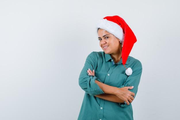 Jeune femme avec les mains croisées en chemise, bonnet de noel et l'air heureux, vue de face.