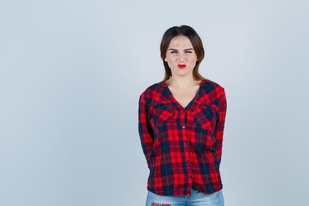 Jeune femme avec les mains derrière le dos tout en fronçant les sourcils en chemise à carreaux et l'air grincheux, vue de face.
