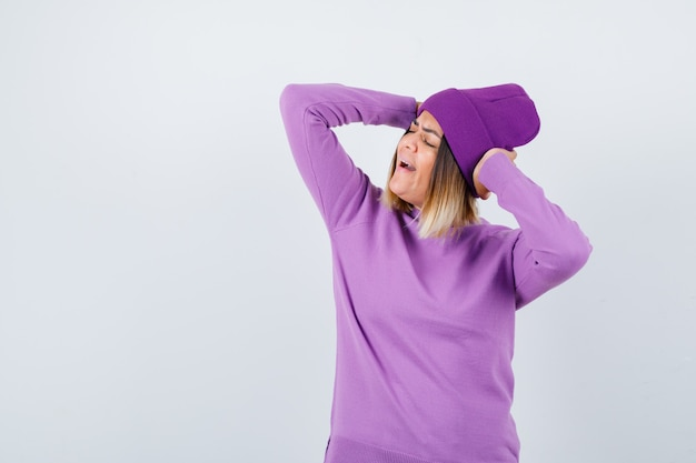 Jeune femme avec les mains derrière la tête en pull violet, bonnet et l'air heureux. vue de face.