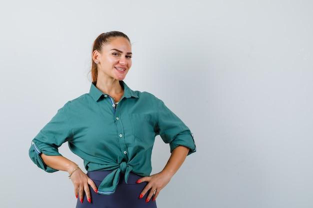 Jeune femme avec les mains sur les hanches en chemise verte et à la gaieté, vue de face.