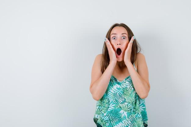 Jeune femme avec les mains sur les joues en blouse et l'air effrayée. vue de face.