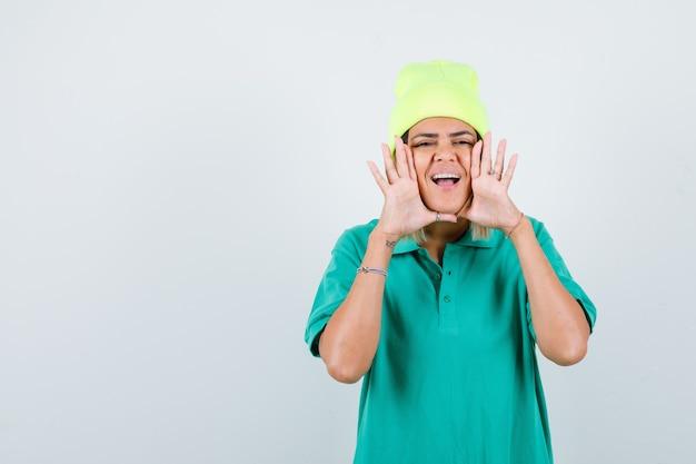 Jeune femme avec les mains près de la bouche en t-shirt polo, bonnet et regardant joyeux, vue de face.