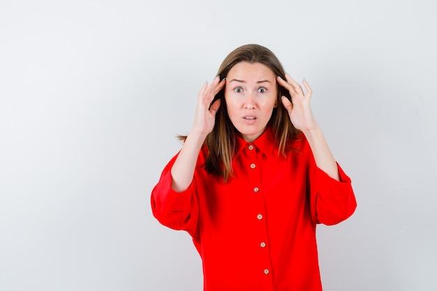 Jeune femme avec les mains près des oreilles en blouse rouge et à la perplexité. vue de face.