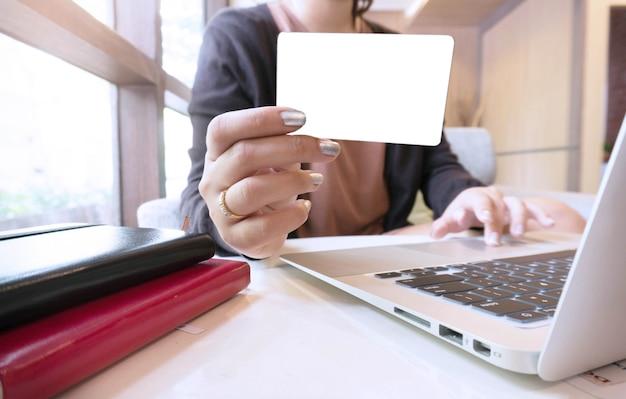 Jeune femme mains tenant une carte de crédit en plastique et utilisant un ordinateur portable. concept d'achat en ligne.