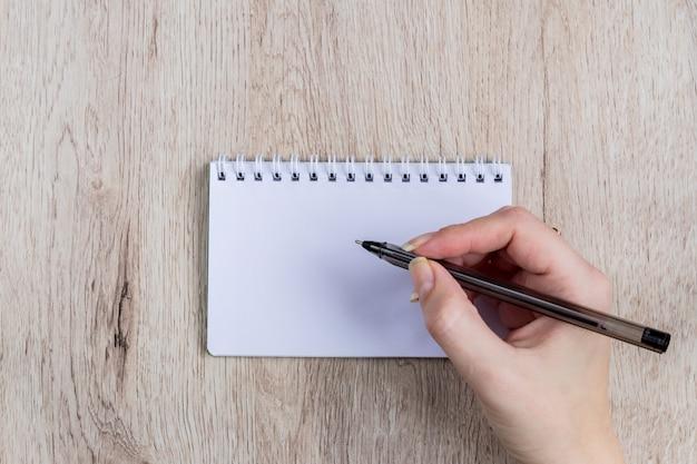 Jeune femme, mains, tenir, ouvert, pages cahier, à, stylo noir, sur, table bois