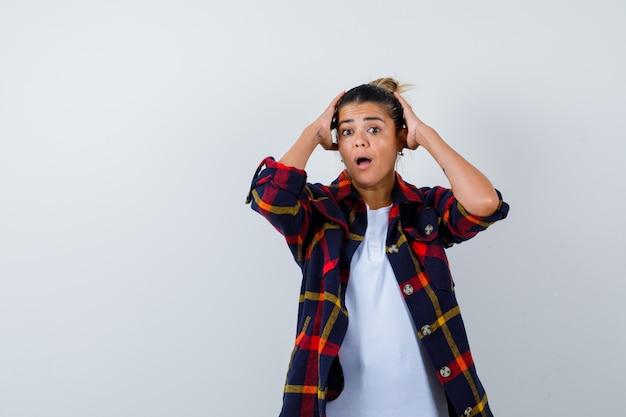 Jeune femme avec les mains sur la tête, la chemise et l'air surpris, vue de face.