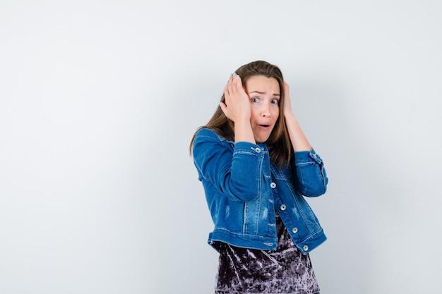 Jeune femme avec les mains sur la tête en chemisier, veste en jean et l'air effrayé. vue de face.