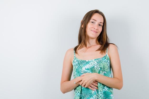 Jeune femme avec les mains sur le ventre en blouse et l'air mignon, vue de face.