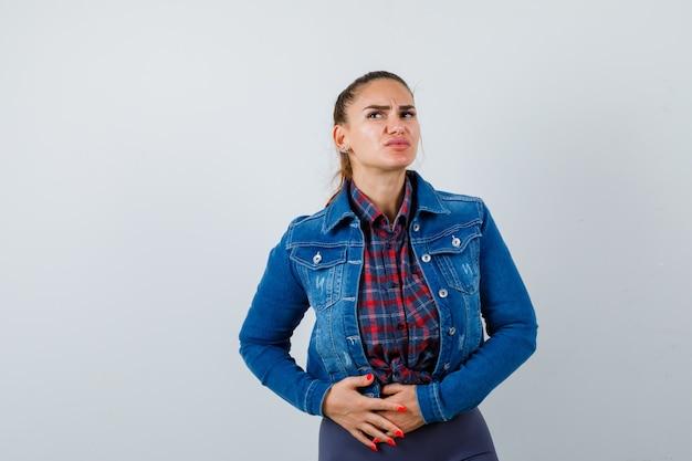 Jeune femme avec les mains sur le ventre en chemise à carreaux, veste en jean et semblant douloureuse, vue de face.