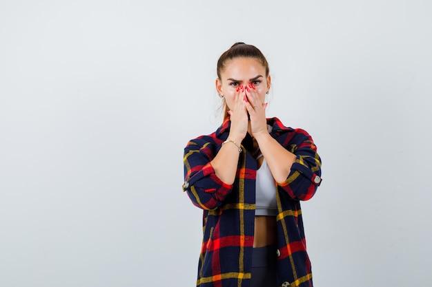 Jeune femme avec les mains sur le visage tout en regardant la caméra dans un haut court, une chemise à carreaux, un pantalon et l'air sérieux. vue de face.
