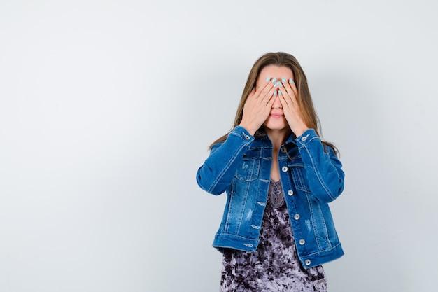 Jeune femme avec les mains sur les yeux en chemisier, veste en jean et l'air mignon, vue de face.