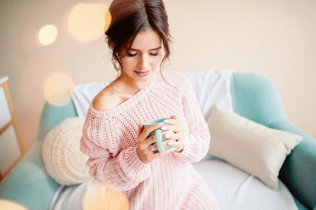 Jeune femme à la maison assis et se détendre dans son salon, boire du café