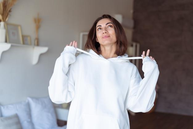 Jeune femme à la maison dans la chambre dans un sweat à capuche blanc chaud, heureuse, posant, souriante, soirée d'hiver confortable