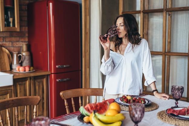 Jeune femme à la maison dans la cuisine, l'eau potable du verre.