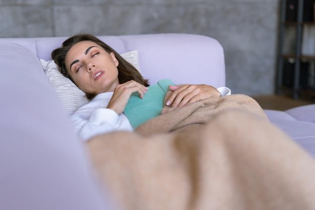Une jeune femme à la maison dans un sweat à capuche blanc sur le canapé s'est enveloppée dans une couverture chaude, s'est endormie en lisant un livre