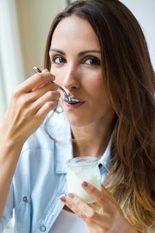Jeune femme à la maison à manger du yaourt