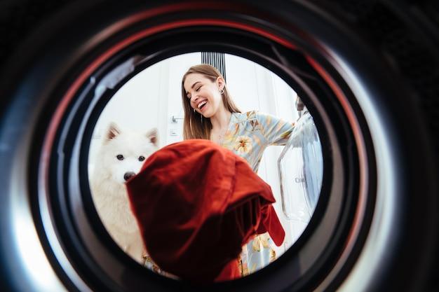 Jeune femme à la maison met la robe dans la machine à sécher.