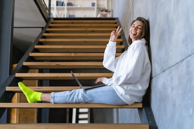 Une jeune femme à la maison vêtue d'un sweat à capuche blanc et d'un jean est assise dans les escaliers avec un ordinateur portable sur les genoux