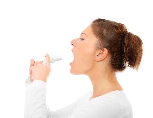 Une jeune femme avec un mal de gorge spray sur fond blanc