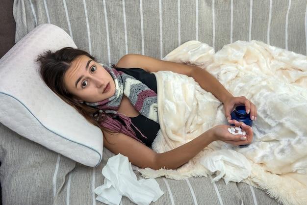 Jeune femme malade avec une forte fièvre et une grippe couchée dans un lit à la maison recouvert d'une couverture