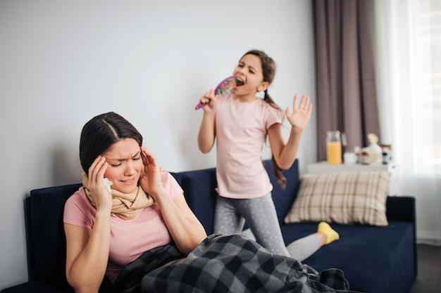 Une jeune femme malade a des maux de tête. ici, ma fille chante à haute voix. l'enfant se tient à genoux sur le canapé et tient la brosse comme micro. jeune femme se tenir la main sur la tête et rétrécir. elle souffre.