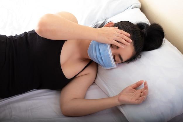 Jeune femme malade mettant un masque médical au repos dormant sur le lit dans la chambre