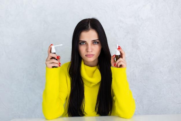 Jeune femme malade tenant un médicament en spray le matin, se sentant mal.