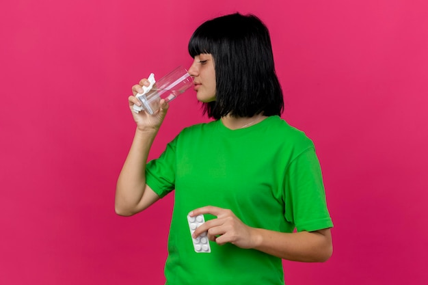 Jeune femme malade tenant un paquet de serviette de comprimés et un verre d'eau potable isolé sur un mur rose avec espace de copie