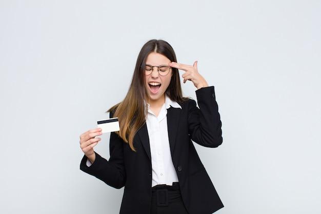 Jeune femme à la malheureuse et stressée, geste de suicide faisant signe de pistolet avec la main, montrant la tête avec une carte de crédit