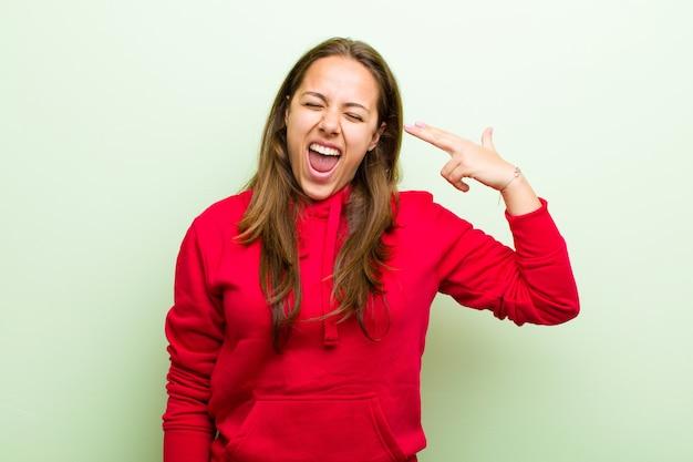 Jeune femme à la malheureuse et stressée, geste de suicide faisant signe de pistolet avec la main, pointant vers la tête